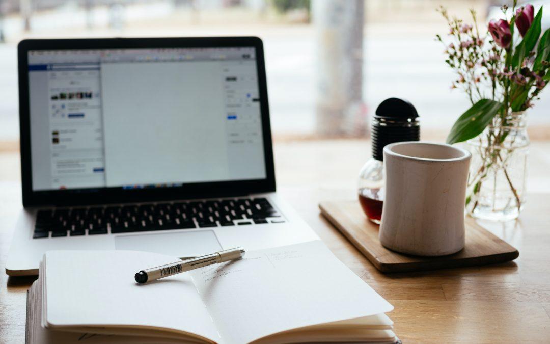 Ordinateur, carnet de notes et infusion sur un bureau de travail